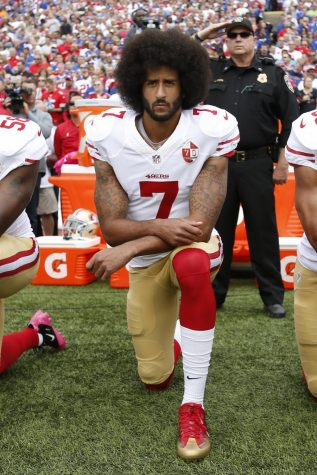 Kaepernick takes a knee during the anthem.